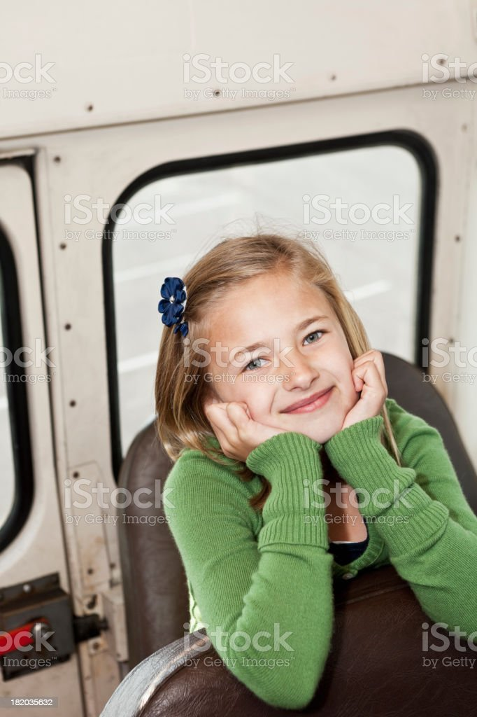 Girl sitting in back seat of school bus stock photo
