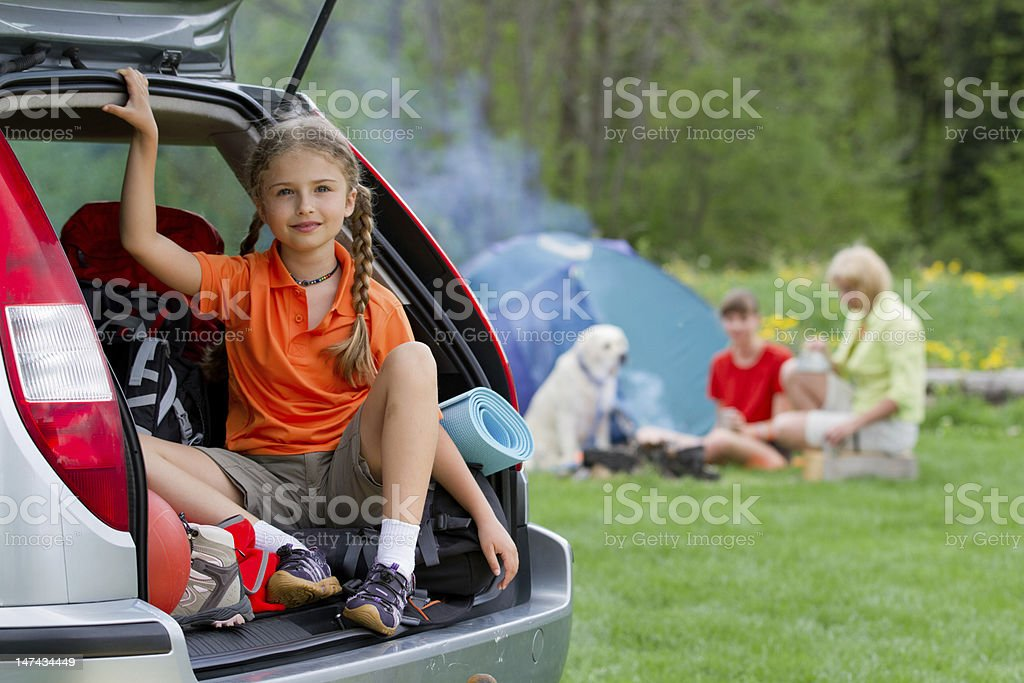 Girl sitting in her car trunk with her family camping behind stock photo