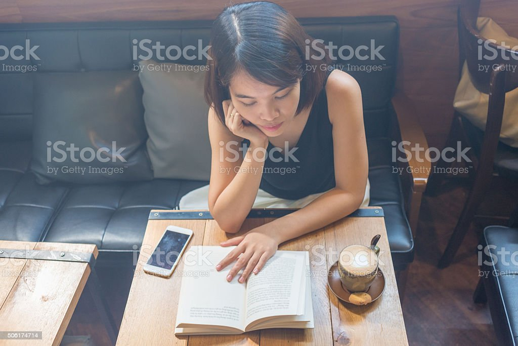 Girl sitting in light music coffee shop and reading book stock photo