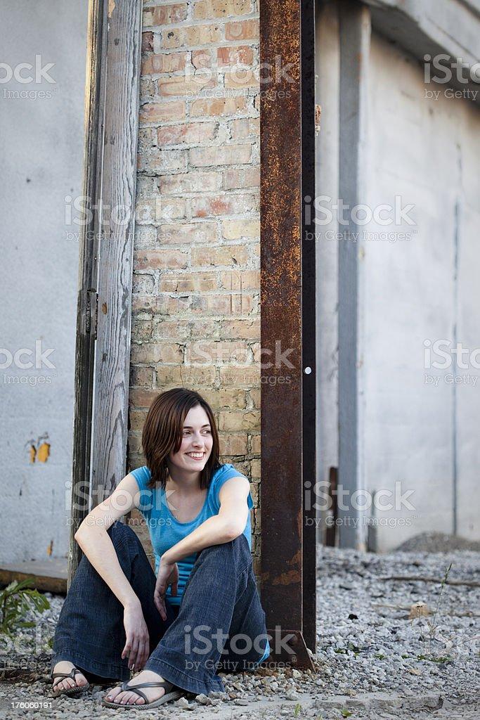 Girl Sitting in Run Down Urban Area royalty-free stock photo