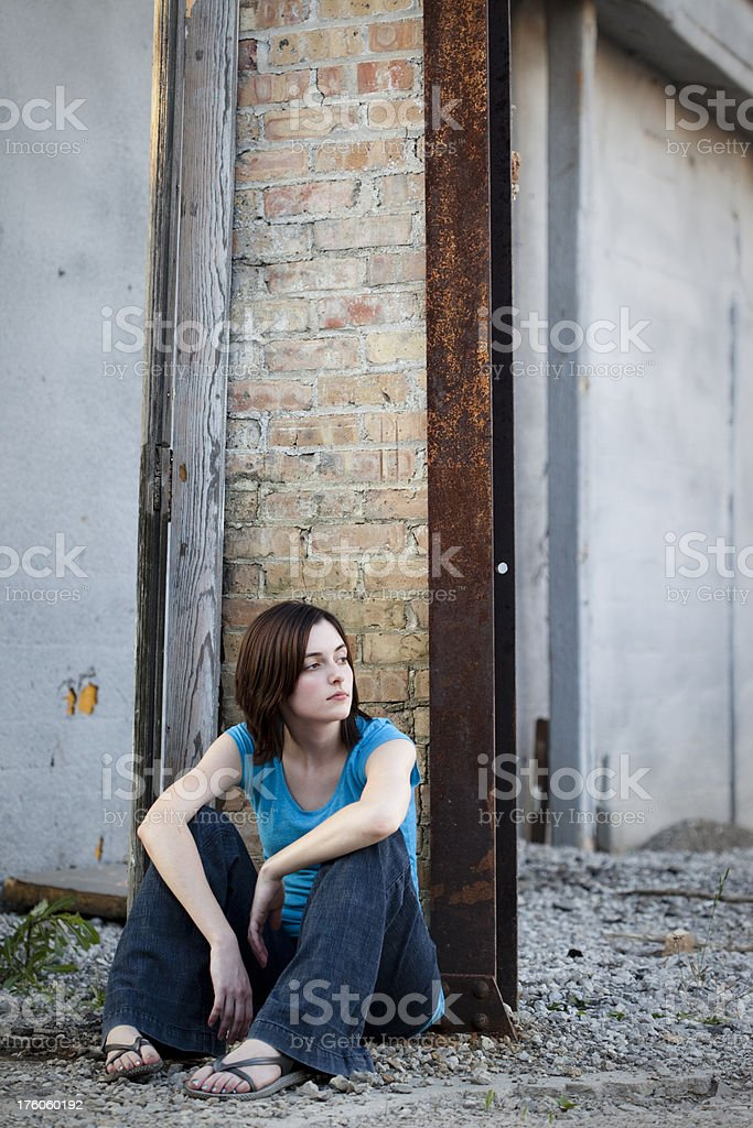 Girl Sitting in Run Down Urban Area royalty-free stock photo