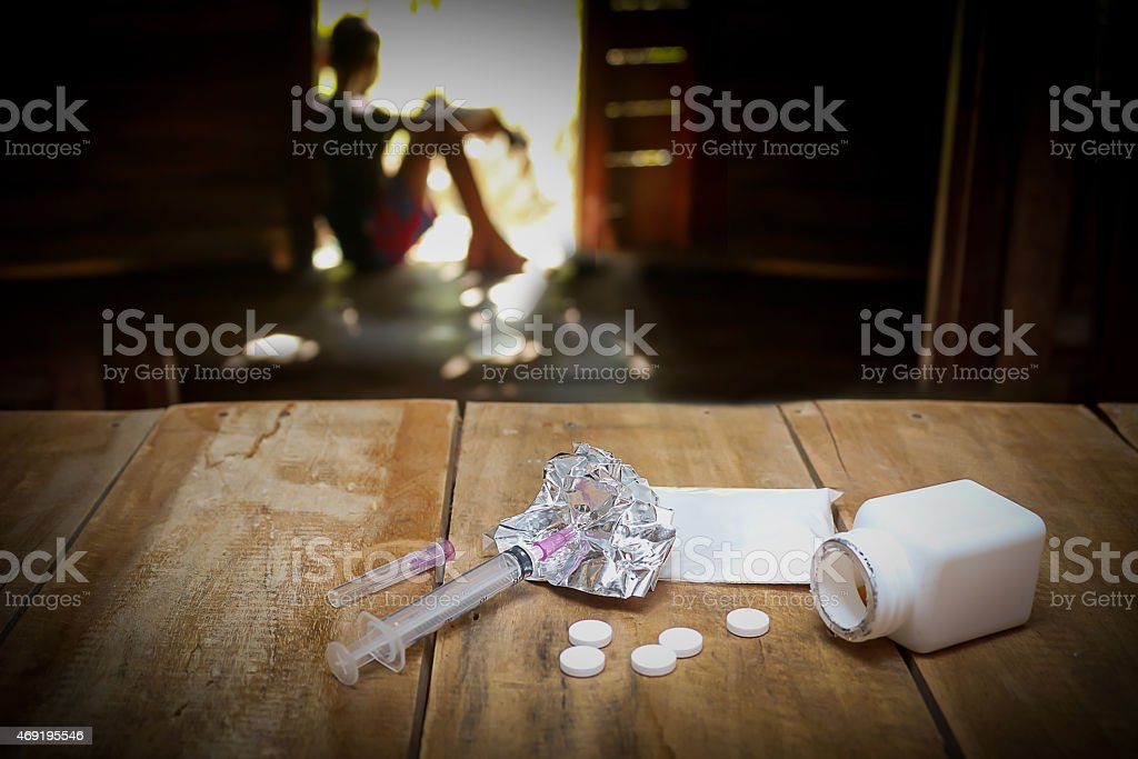 Girl sitting in the background, with drugs on the table stock photo