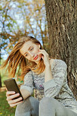 Girl sitting in the park and makes selfie