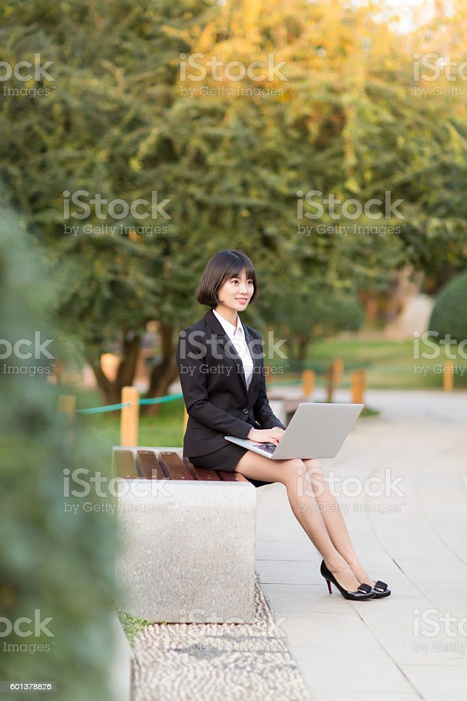 girl sitting in the park bench stock photo