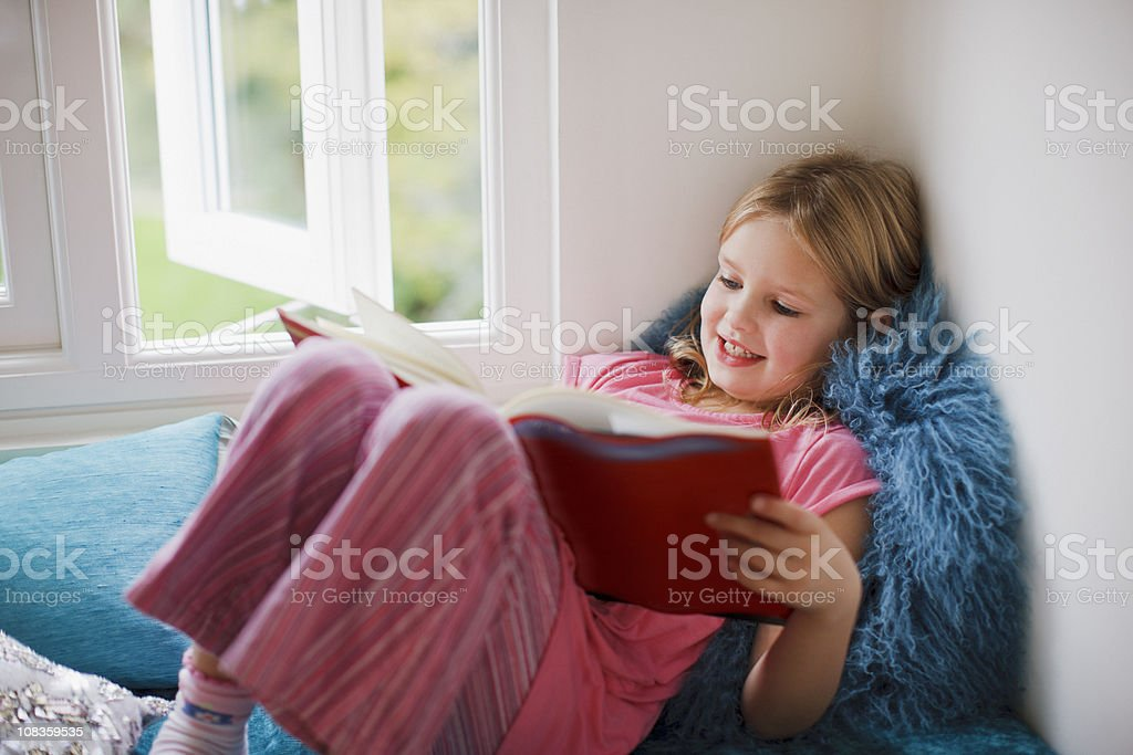 Girl sitting in window seat reading book royalty-free stock photo