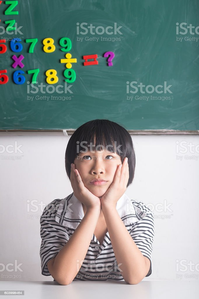 girl sitting infront of  blackboard with numbers stock photo