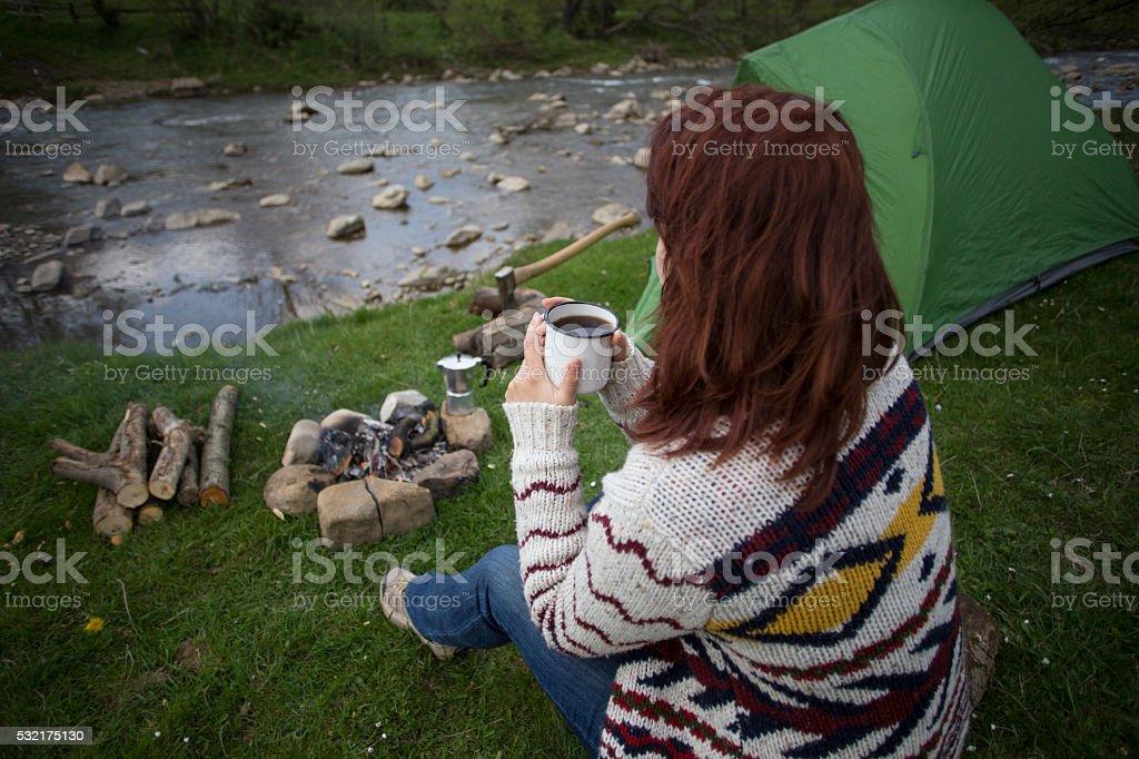 Girl sitting near a campfire. stock photo