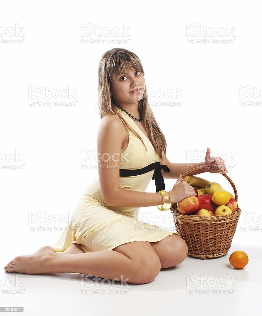 Girl sitting near fruit basket royalty-free stock photo