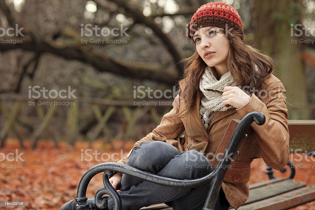 girl sitting on a bench  in the autumn park royalty-free stock photo