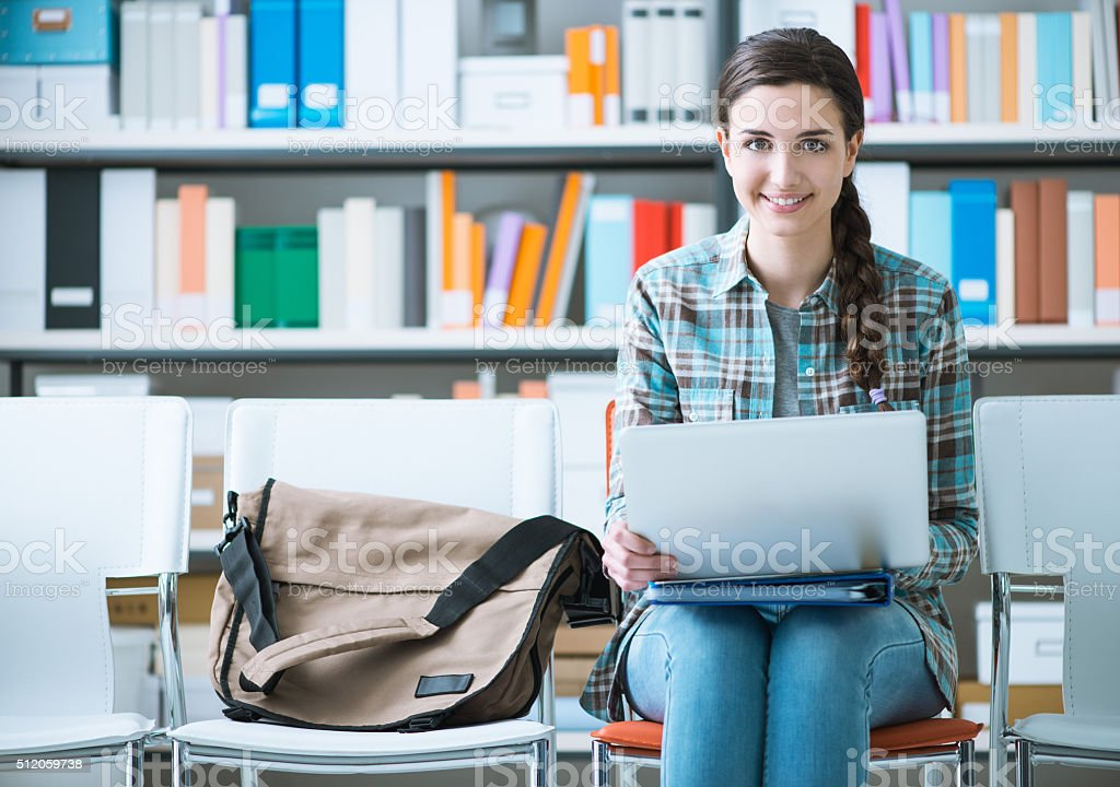 Girl sitting on a chair and using a laptop stock photo