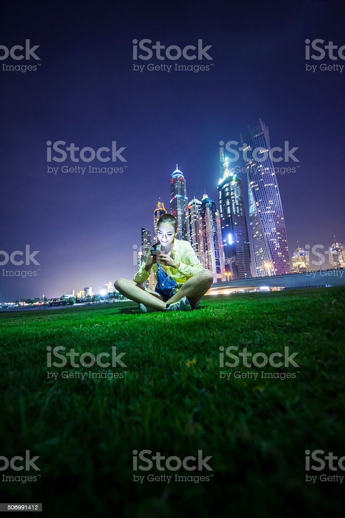 Girl sitting on a grass field in front of  cityscape stock photo