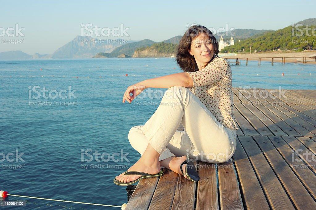 girl sitting on a pier near  sea royalty-free stock photo