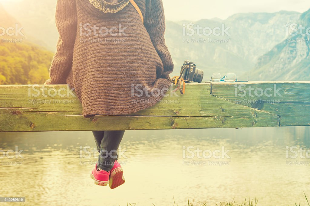 Girl sitting on a wooden pier near water. stock photo