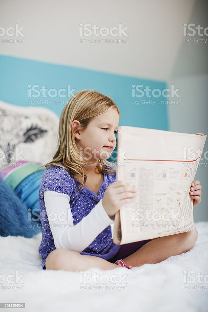 Girl sitting on bed reading newspaper royalty-free stock photo