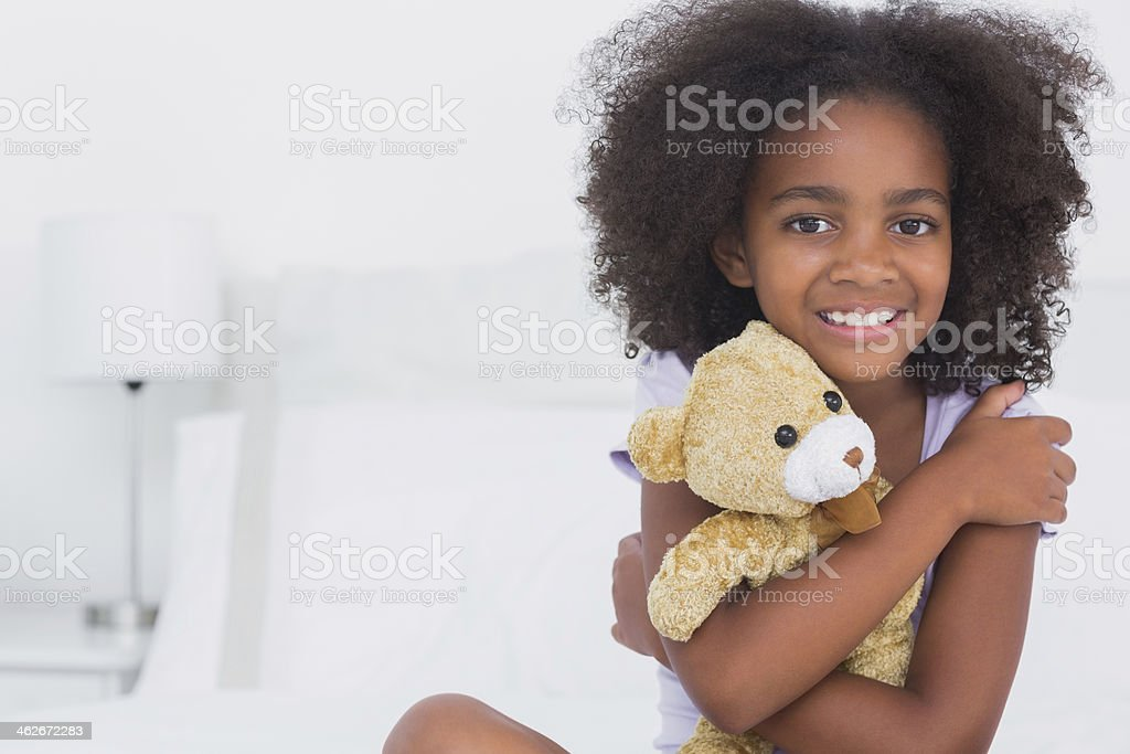 Girl sitting on bed smiling at camera holding teddy bear stock photo