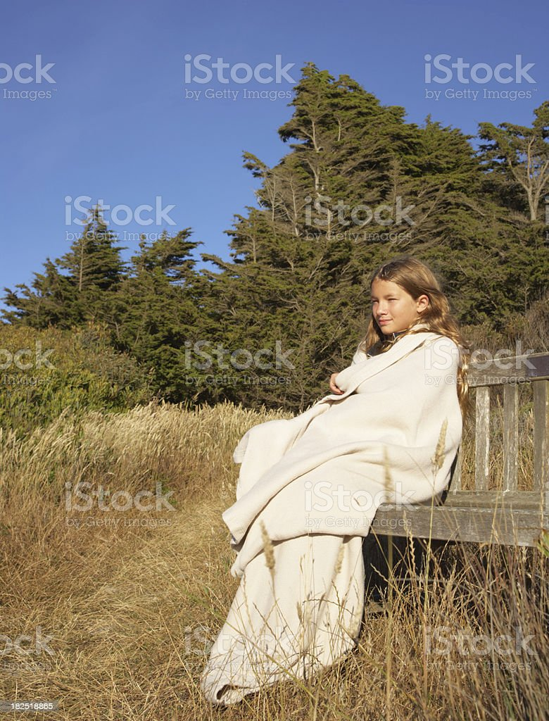 Girl Sitting on Bench in a Meadow royalty-free stock photo