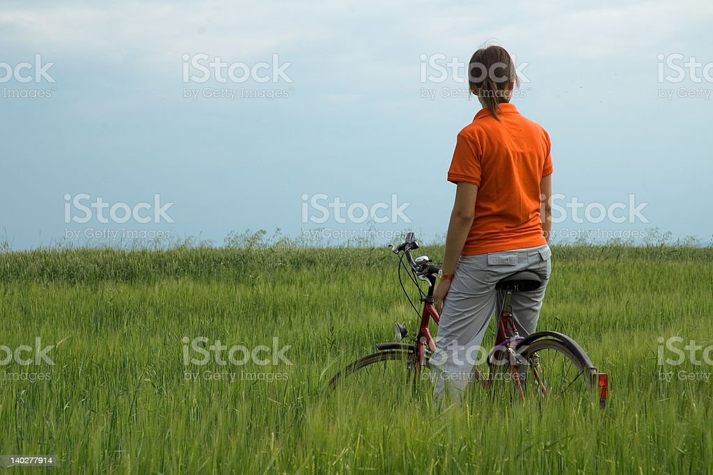 girl sitting on bicycle in green field royalty-free stock photo