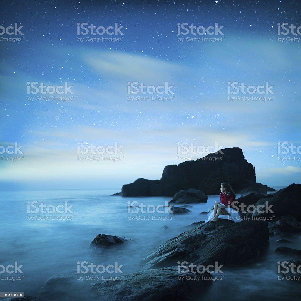 Girl Sitting on black rocks royalty-free stock photo
