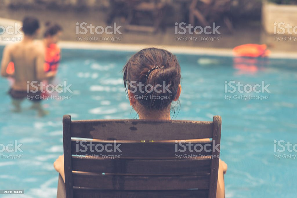 Girl sitting on chair watching friends playing on swimming pool stock photo
