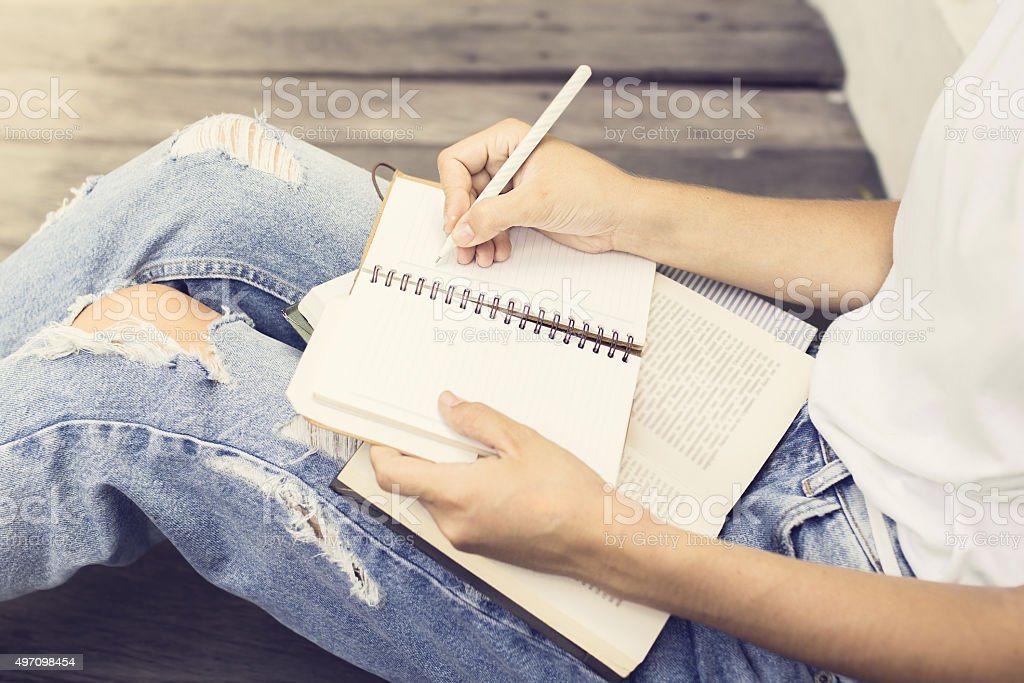 Girl sitting on floor and wrote in a notebook stock photo