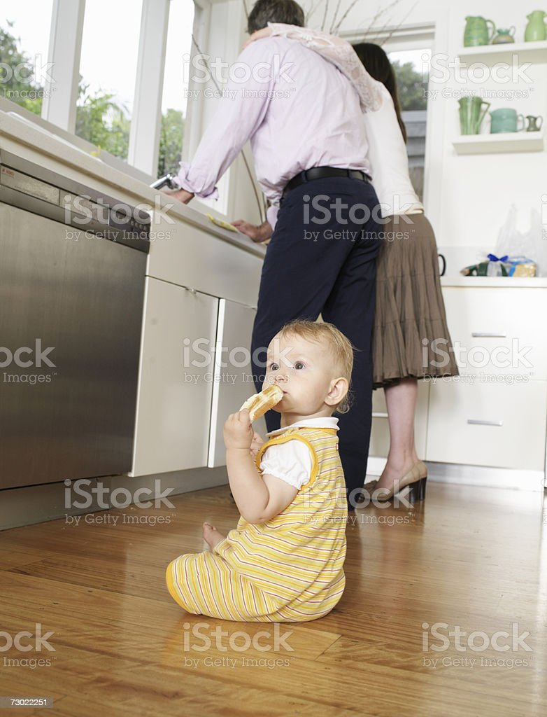 Girl (9-12 months) sitting on floor in kitchen parents standing in background stock photo