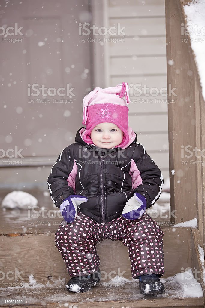 Girl Sitting on Front Step in Snow royalty-free stock photo