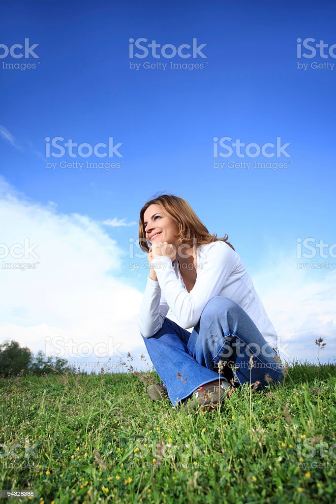 Girl sitting on green grass. royalty-free stock photo