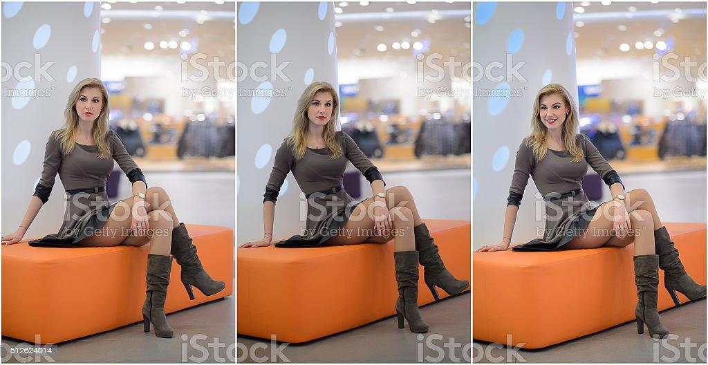 girl sitting on orange bench in modern shopping center stock photo