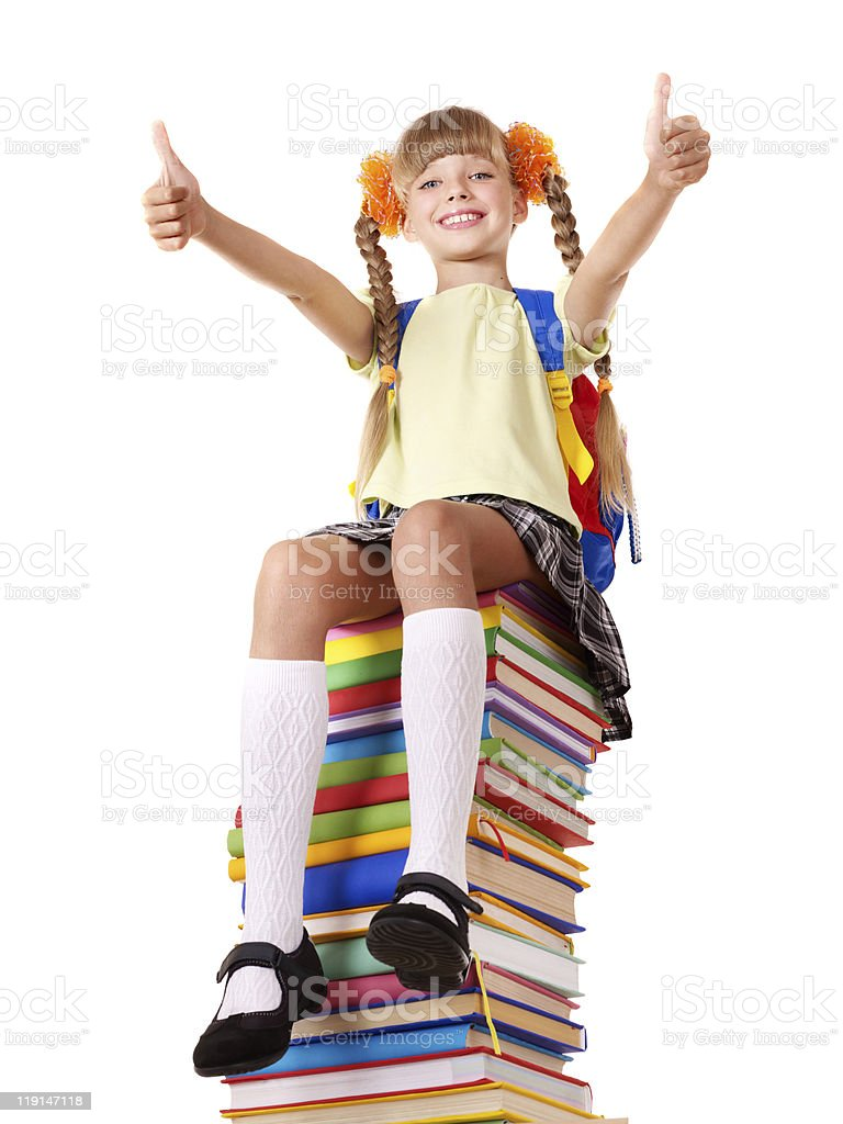 Girl sitting on pile of books showing thumbs up. royalty-free stock photo