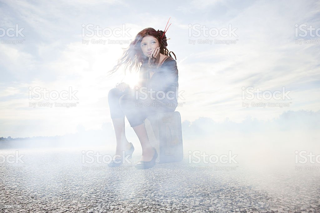 Girl sitting on suitcase in cloud of smoke stock photo