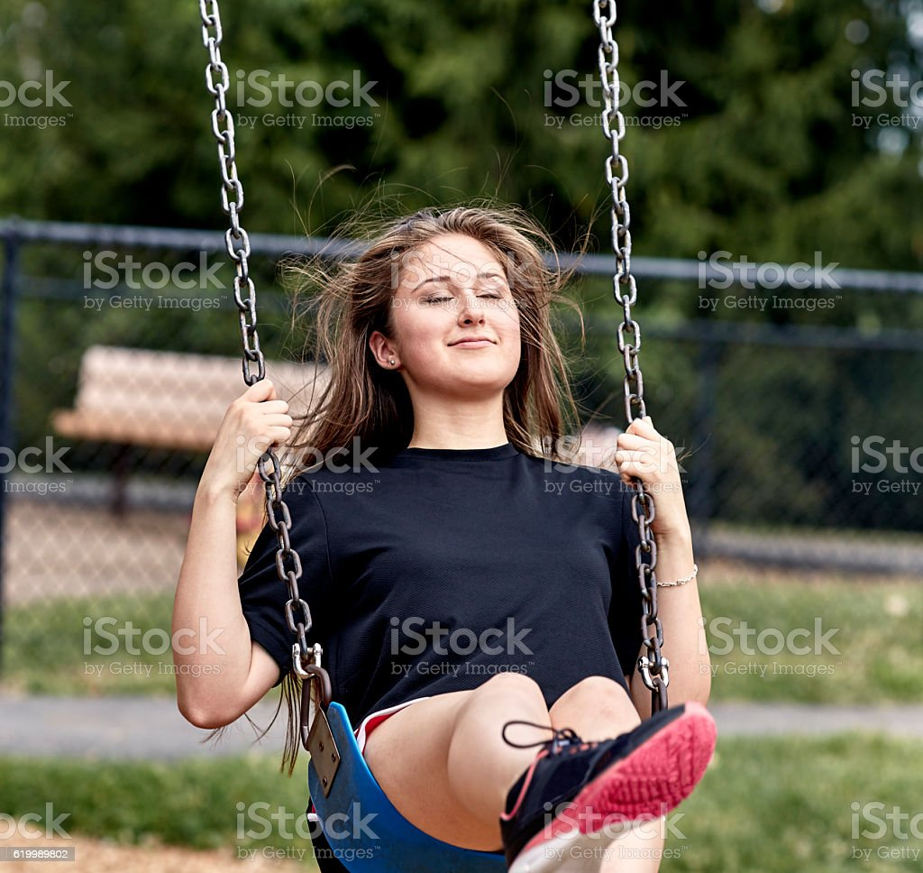Girl sitting on Swing in Playground stock photo
