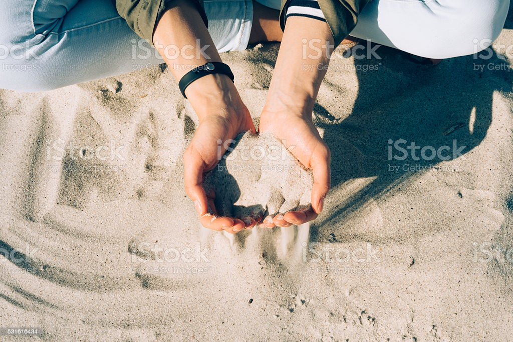 Girl sitting on the beach and sand passes through palm stock photo