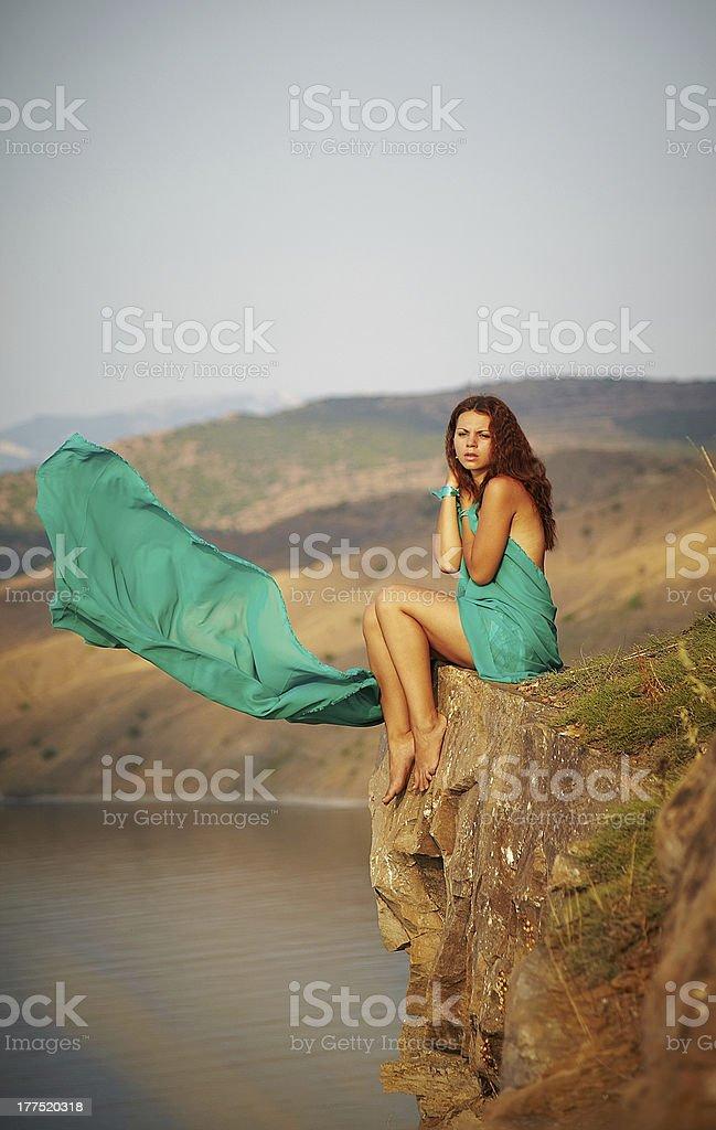Ragazza seduta sul bordo di una scogliera foto stock royalty-free
