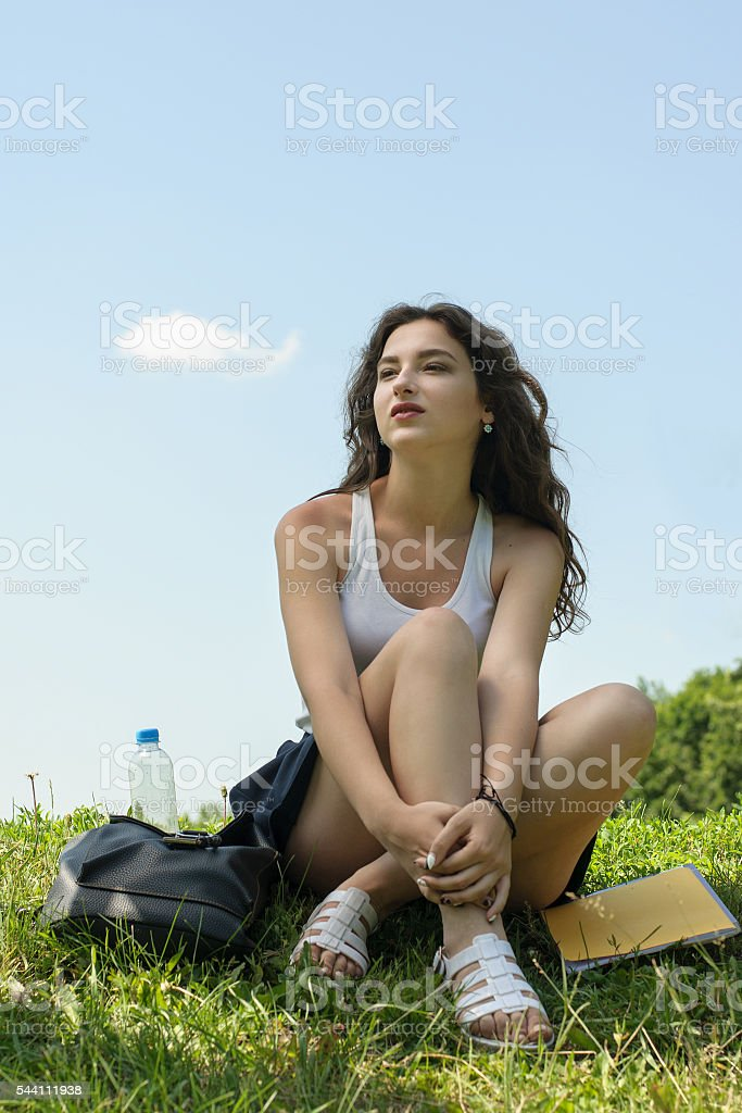 Girl sitting on the grass after school stock photo