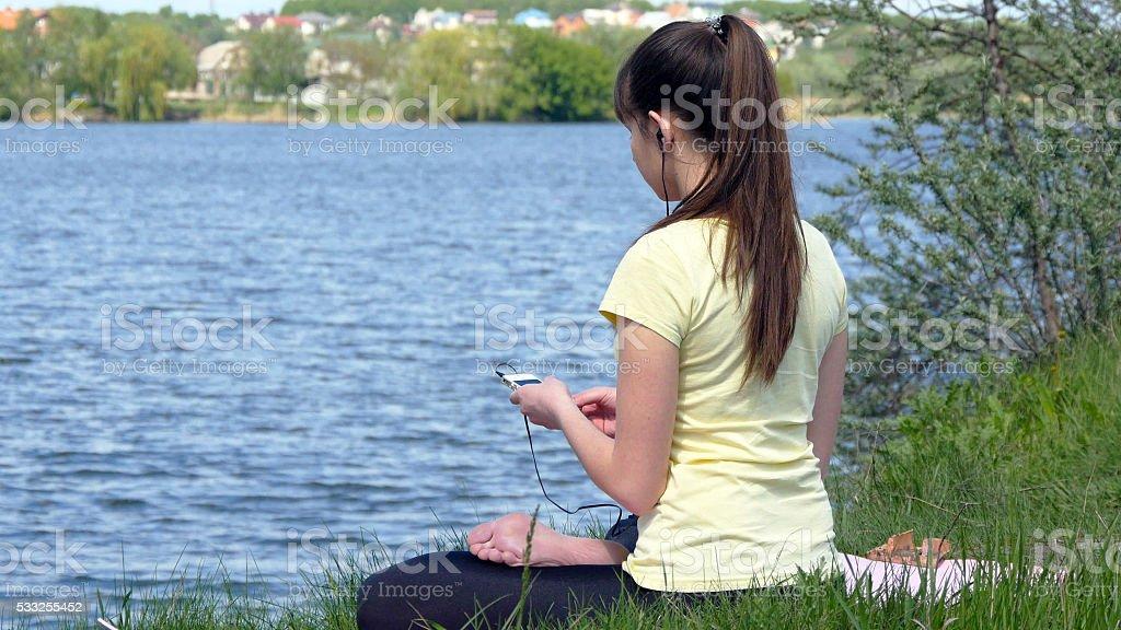 Chica sentada en el césped y relajante Meditando foto de stock libre de derechos