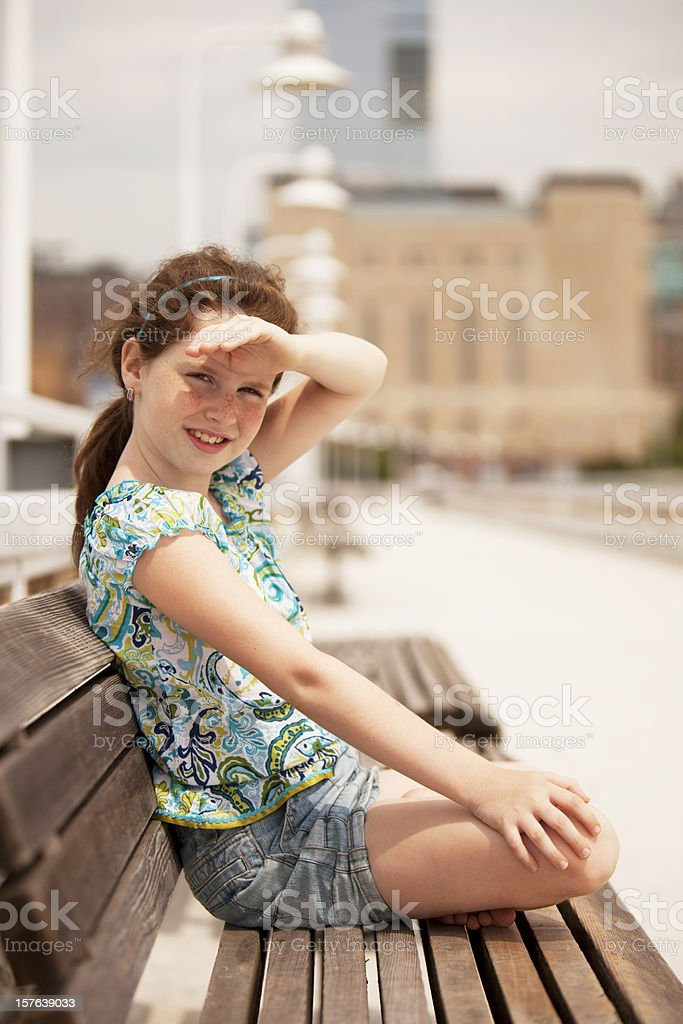A girl sitting on the pier looking through sunny day stock photo