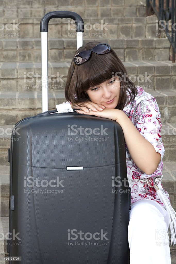 Girl sitting on the stairs with a suitcase royalty-free stock photo