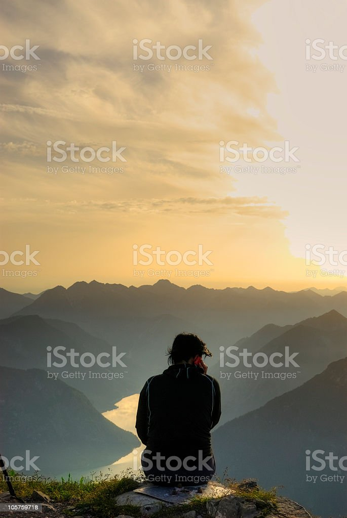 Girl sitting on the top of a mountain stock photo