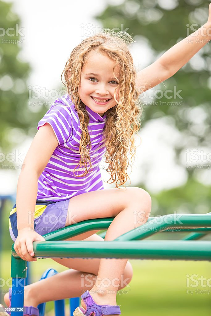 Girl Sitting on Top of Jungle Gym at Playground stock photo