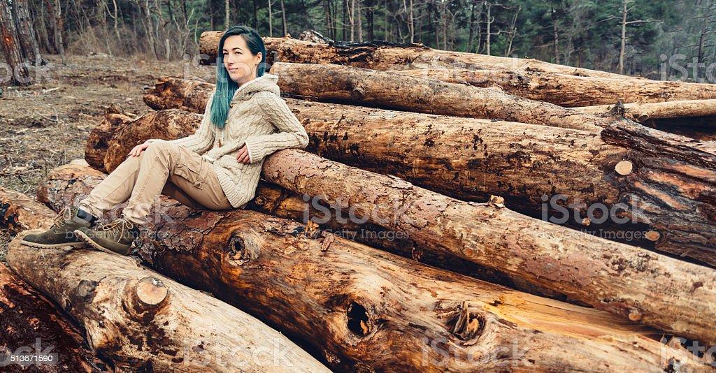 Girl sitting on tree trunk stock photo