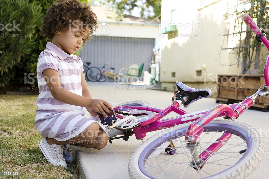 Girl sitting with bicycle in driveway royalty-free stock photo