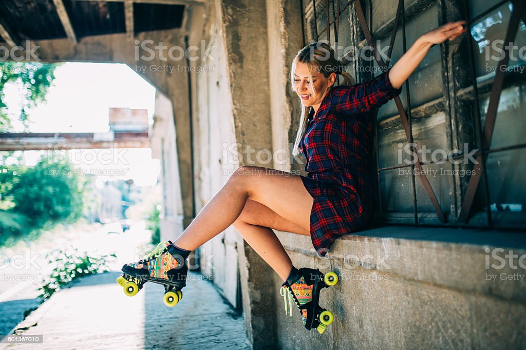 Girl sitting with roller skates stock photo