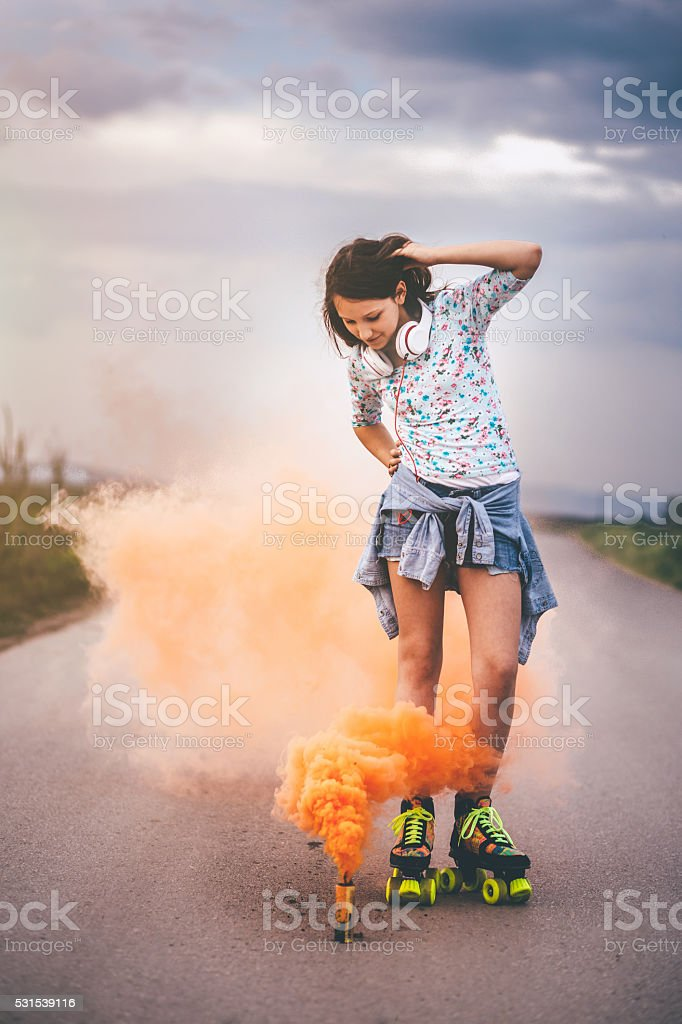 Girl skating surrounded with orange colored smoke grenade stock photo