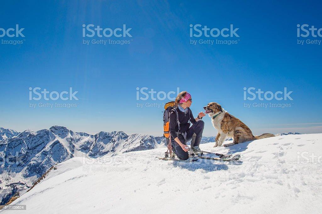 Girl ski touring with his dog stock photo