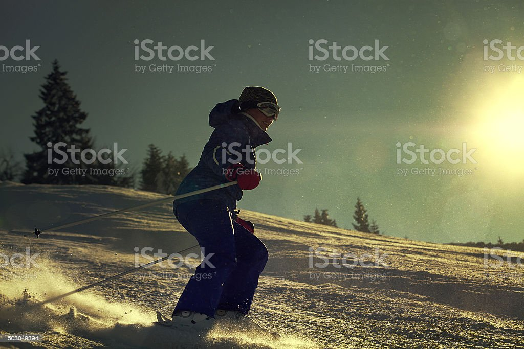 Girl skier slade down on the snow hill stock photo