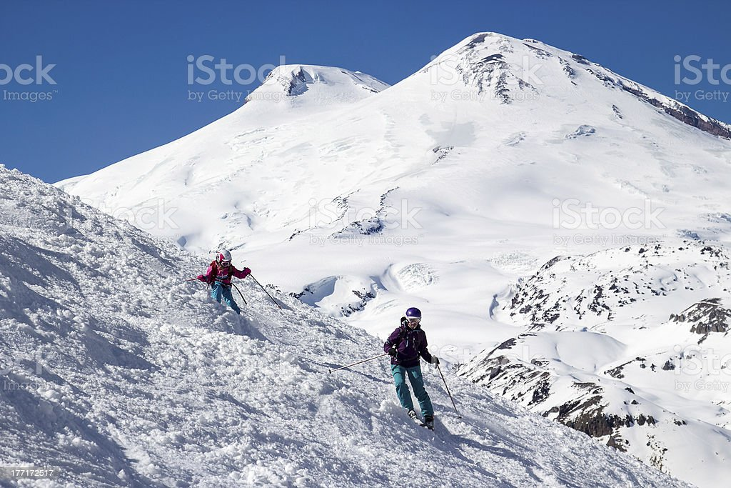 Girl skier with his mother in the mountains royalty-free stock photo