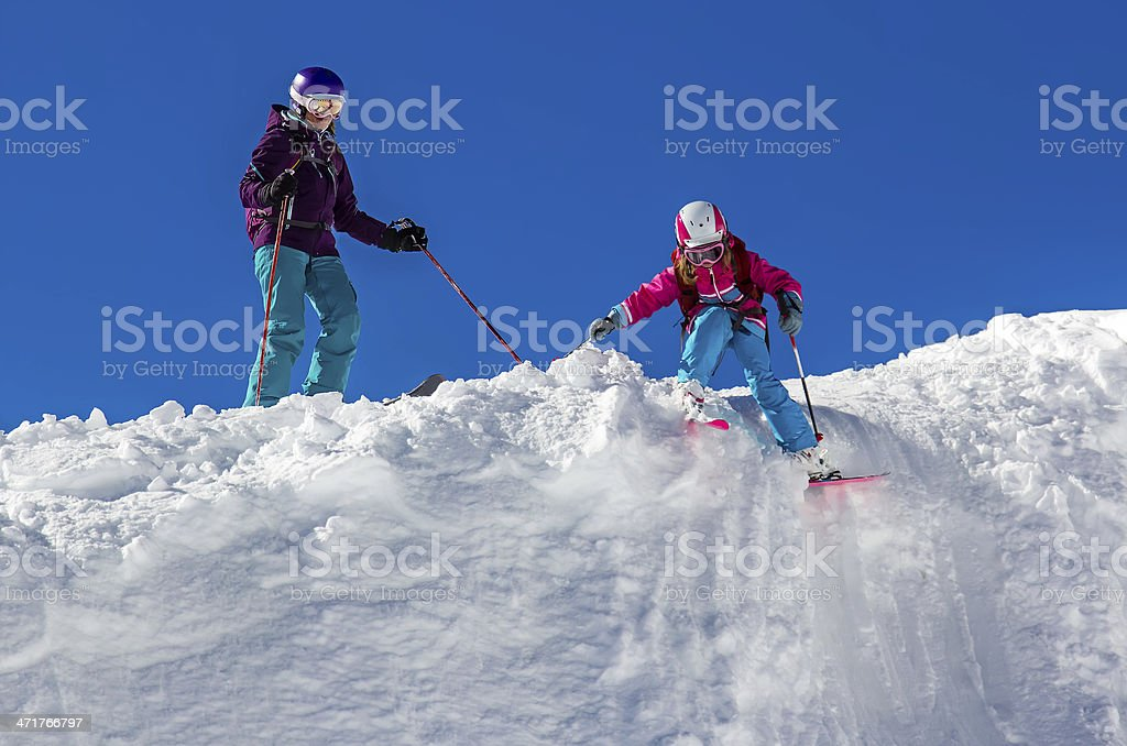 Girl skier with his mother on a steep slope royalty-free stock photo