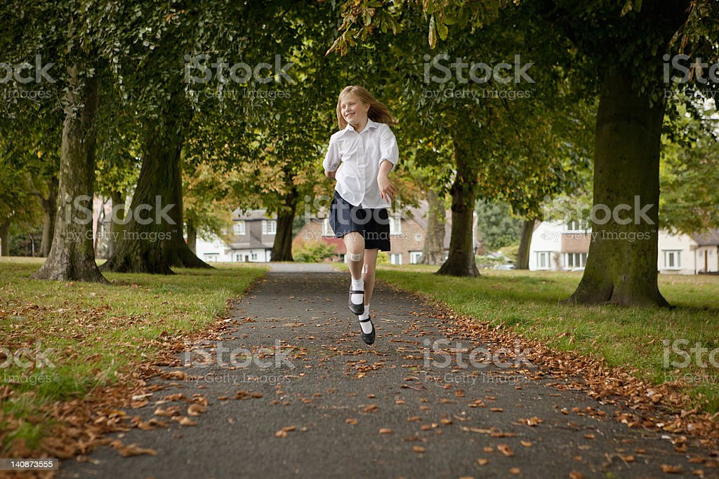 Girl skipping on road in park stock photo