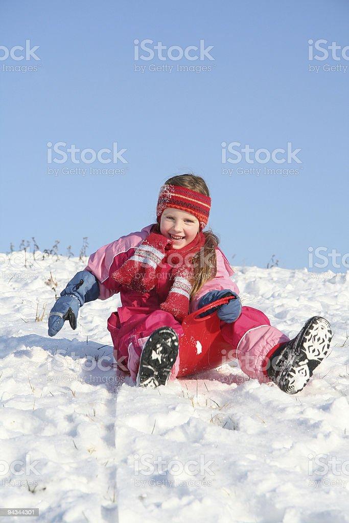 Girl sleeding down a snowy hill stock photo