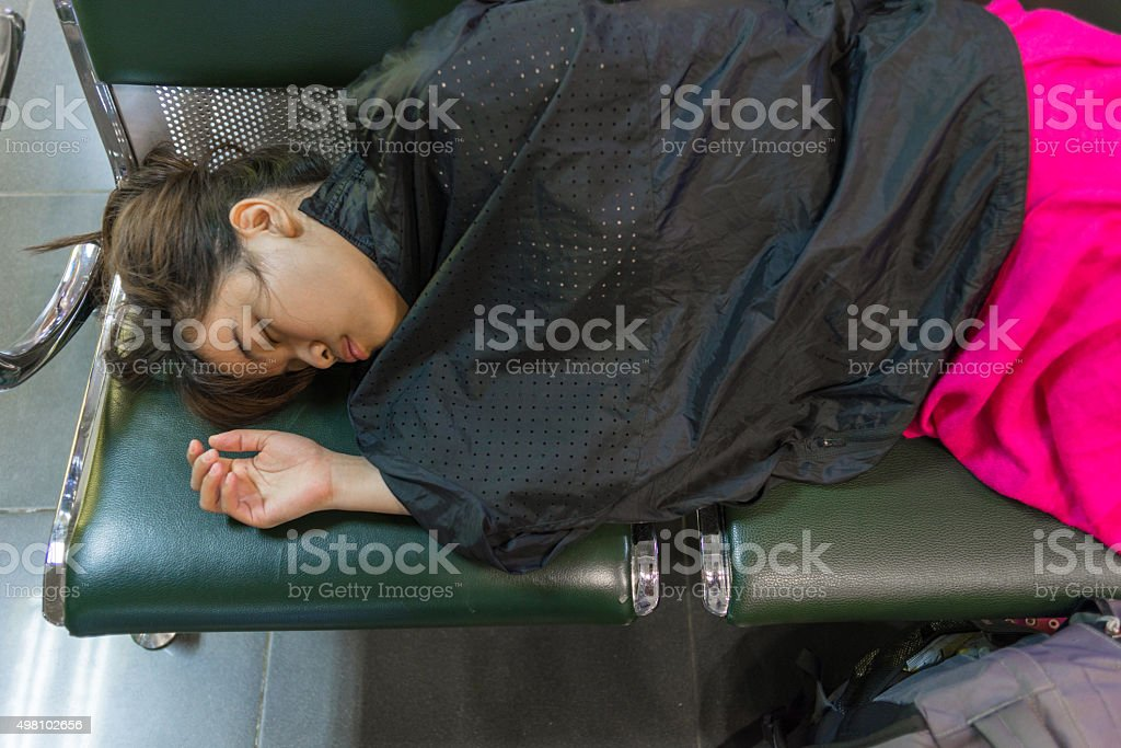Girl sleeping on bench with the jacket covering her body stock photo